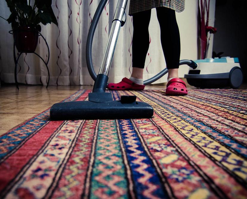 Photo of a woman vacuuming.