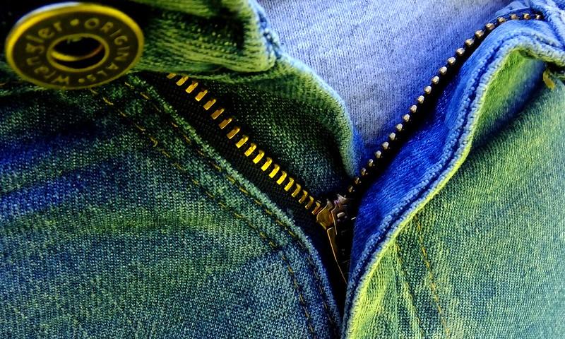 Photo of an unzipped denim fly.