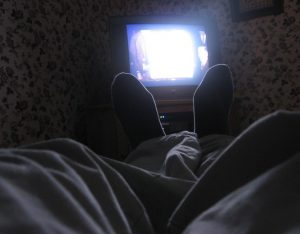 Photograph of feet silhouetted by the glare of the television.