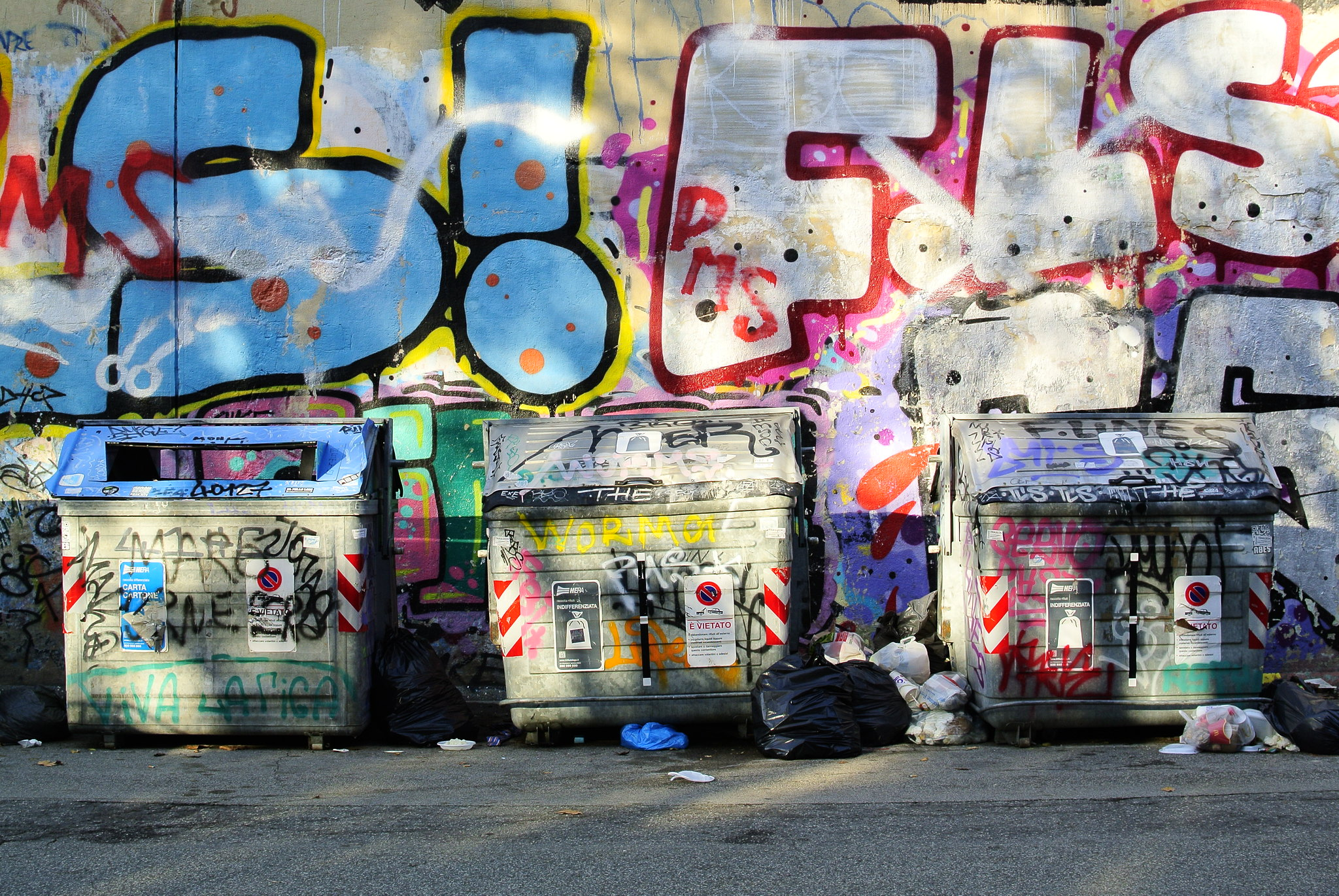 Dumpsters in a grafitti-covered alley.