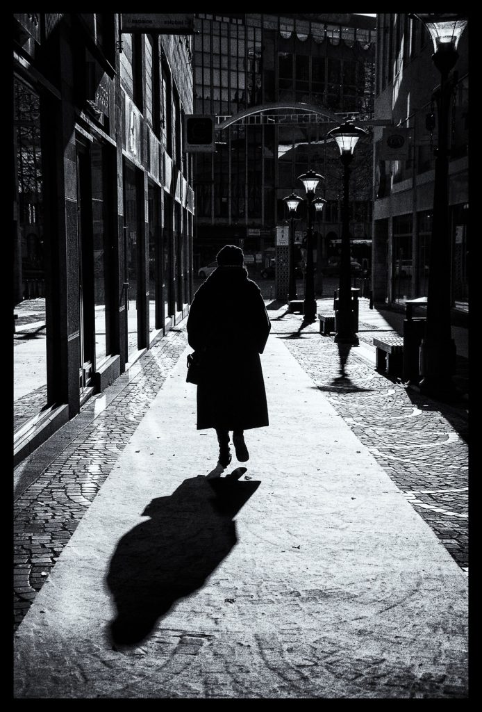 Black and white silhouette of a woman walking.