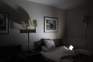 Photo of rumpled bed lit by a computer screen.