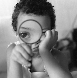 Image of a child looking through a magnifying glass.