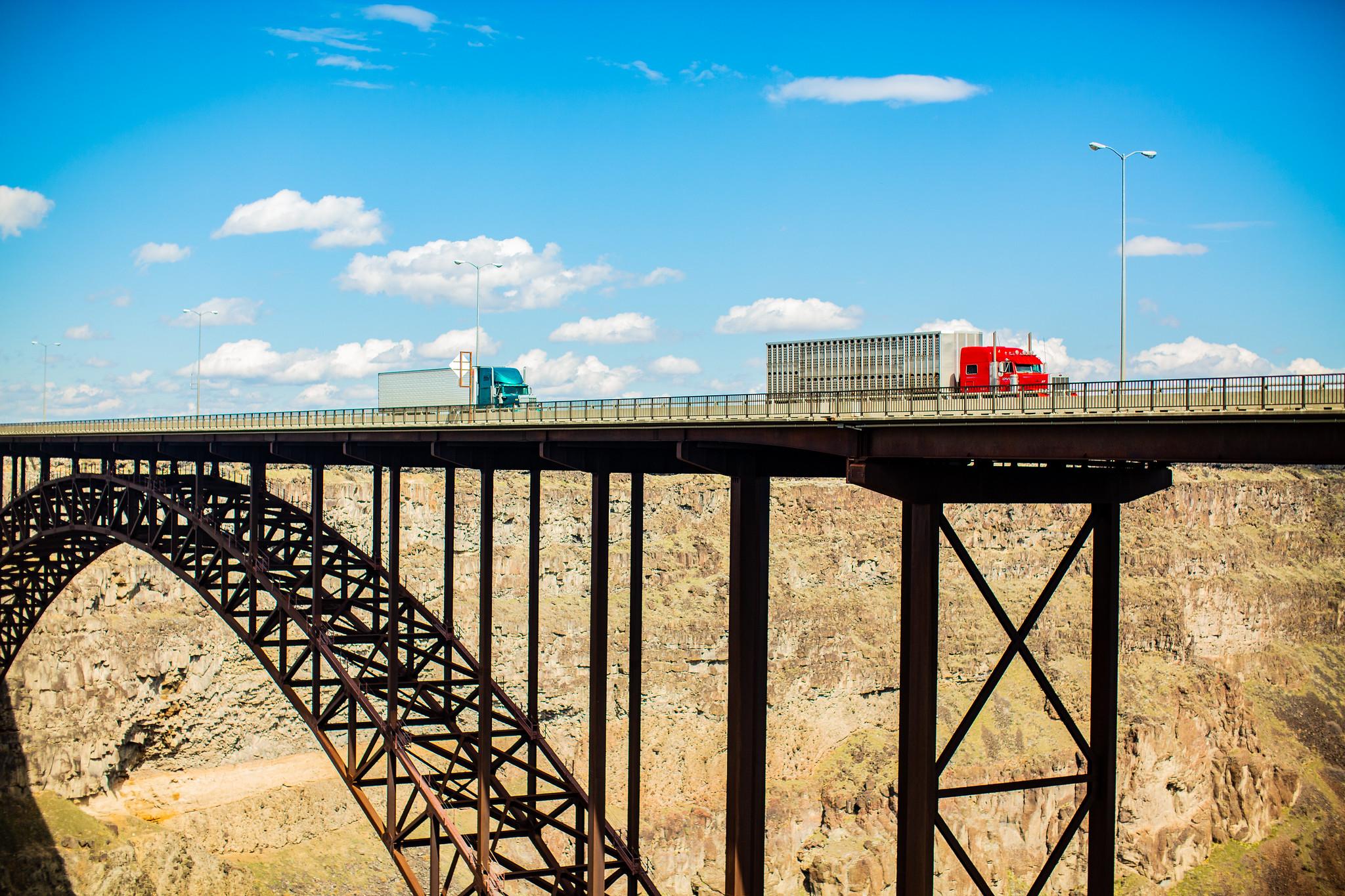Photo of two trucks on a bridge.