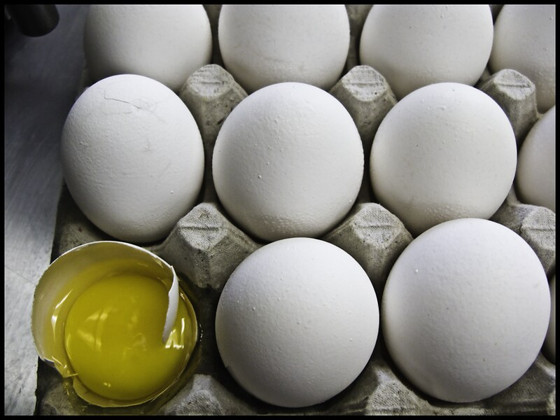 Image of eggs in a carton, with one broken open.